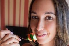 女孩拿着一把叉子在与切片的嘴蕃茄 免版税库存照片