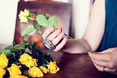 女孩拿着一朵黄色玫瑰 库存照片