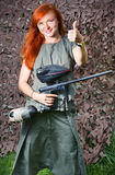 女孩拿着一杆迷彩漆弹运动枪 免版税库存图片