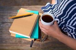 女孩拿着一杯咖啡并且坐公园长椅 写和书的笔记本 研究、工作和企业概念 库存图片