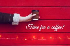 女孩拿着一杯咖啡或茶 免版税库存照片