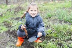 女孩拿着一棵红萝卜 图库摄影