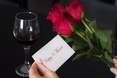 女孩拿着与消息愉快8的一个纸牌 3月在她的手和红色玫瑰和酒杯上在黑桌上 免版税库存照片