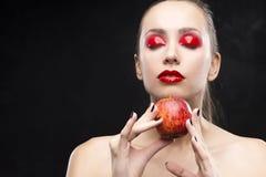女孩拿着与用光泽盖的红色眼影膏的苹果 库存照片