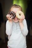 女孩拿着两个油炸圈饼 图库摄影