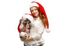 女孩拿着中国有顶饰狗 女孩和狗在圣诞老人` s红色圣诞老人帽子穿戴 查出 免版税库存照片