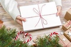 女孩拿着儿童` s圣诞节信件 与礼物盒和圣诞节装饰的圣诞节信件 库存图片