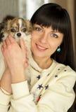 女孩拿着在她的胳膊的一条狗 免版税库存照片