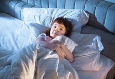 女孩拿着在床上的一床被子 免版税库存图片