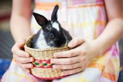 女孩拿着在篮子的一个兔宝宝 免版税图库摄影