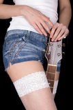 女孩拿着在他的腿之间的一把吉他 免版税库存照片