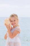女孩拿着少许壳 免版税库存图片