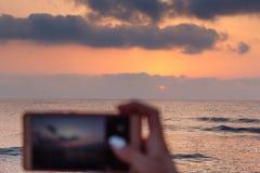 女孩拿着巧妙的电话的` s手拍在海滩的日落照片 手机有日落视图 图库摄影