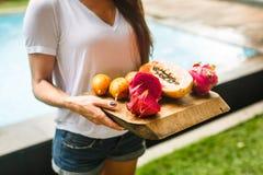女孩拿着异乎寻常的果子木盘子  免版税库存照片