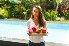 女孩拿着异乎寻常的果子盘子在别墅的 免版税库存图片
