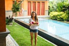 女孩拿着异乎寻常的果子盘子在别墅的 图库摄影