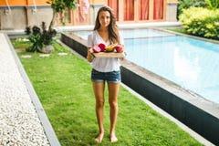 女孩拿着异乎寻常的果子盘子在别墅的 免版税图库摄影