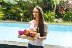 女孩拿着异乎寻常的果子盘子在别墅的 免版税库存照片