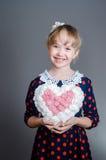 女孩拿着心脏手中并且微笑 免版税库存图片
