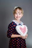女孩拿着心脏手中并且微笑 免版税图库摄影
