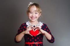 女孩拿着心脏手中并且微笑 图库摄影