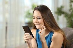 女孩拿着智能手机的横穿手指 免版税库存照片