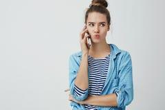 女孩拿着智能手机的谈的电话听力热的新谣言说闲话的激动的被吸引的,听的有趣的新闻 免版税库存图片