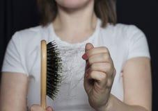 女孩拿着有她的头发的一把梳子在她前面 头发空白查出的问题 掉头发 免版税库存照片