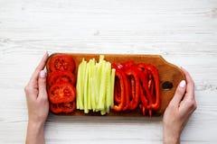 女孩拿着有新近地被切的菜的一个委员会:蕃茄 免版税库存照片