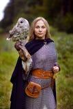 女孩拿着猫头鹰的锁子甲在森林里 免版税库存图片