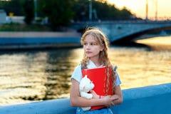 女孩拿着玩具熊的少年金发碧眼的女人在日落在城市 免版税库存照片