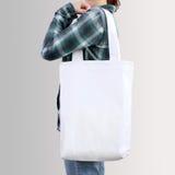 女孩拿着空白的棉花大手提袋,设计大模型 免版税库存图片