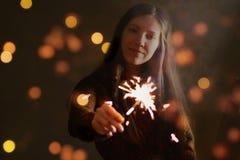 女孩拿着闪烁发光物的` s手 在黑暗 晚上 隔绝  库存照片