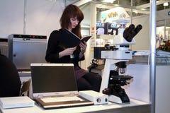 女孩指令未认出显微镜的读取 免版税库存照片