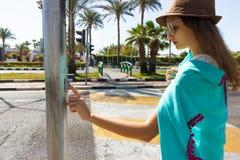 女孩按在路的一个行人交叉路按钮 等待绿灯 免版税库存图片