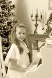 女孩按钢琴的键 图库摄影