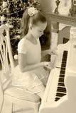 女孩按钢琴的键 免版税库存照片