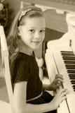 女孩按钢琴的键 库存照片