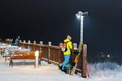 女孩挡雪板在山坡站立反对黑暗的天空 免版税库存照片