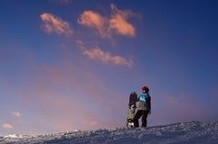 女孩挡雪板在山坡站立反对黑暗的日落天空 免版税库存图片
