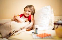 女孩捉住了流感和饮用的热的茶用柠檬在床上 库存照片