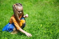 女孩捉住在草坪的一只蚂蚱 库存照片
