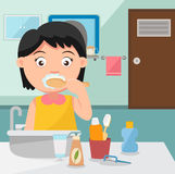 女孩掠过的牙在卫生间里 免版税库存照片