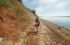 女孩探索在北方针叶林森林里位于的河的陡峭的岩石河岸 库存照片