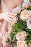 女孩接触开花的分支用手 玫瑰在家 淫荡春天绽放  接触自然纤巧  嫩女孩的 库存照片