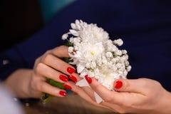 女孩接近的画象修剪举行小逗人喜爱的花花束有限的景深的手 免版税库存照片