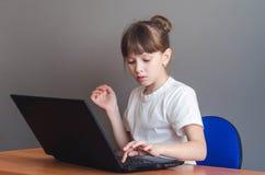 女孩推挤入膝上型计算机 库存图片