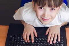 女孩推挤入膝上型计算机 免版税库存图片