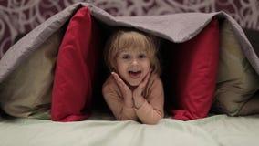 女孩掩藏在毯子和枕头下在床上 隐藏处的概念 股票视频