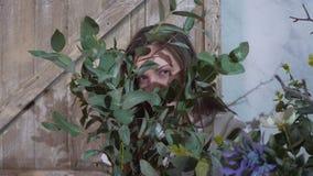 女孩掩藏她的在束的眼睛玉树后 免版税图库摄影